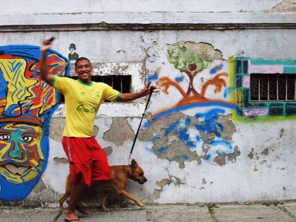 A boy and his dog running in front of graffiti.