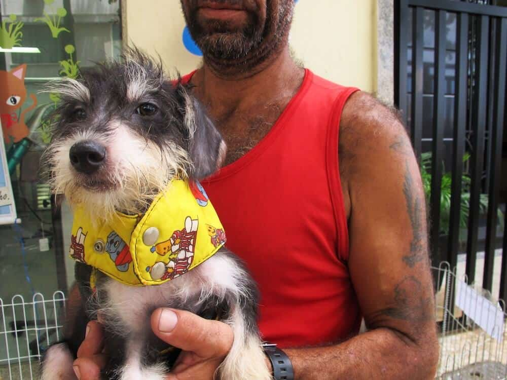 A man showing off a puppy.