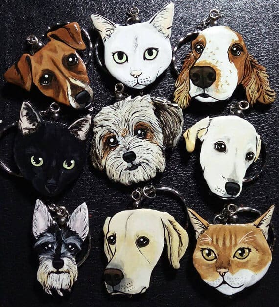 A group of custom painted keychains of dogs and cats.