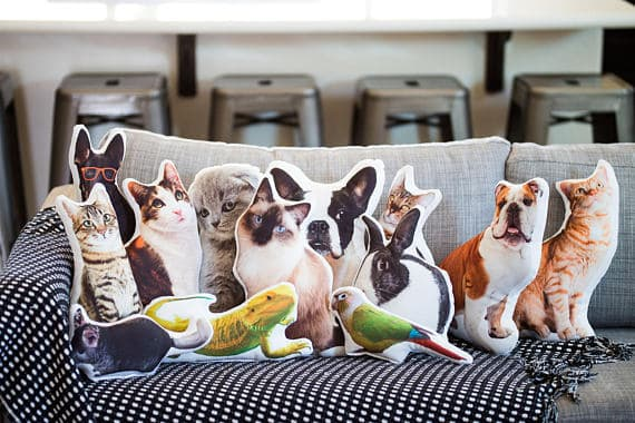 A couch full of custom pillows of pets.
