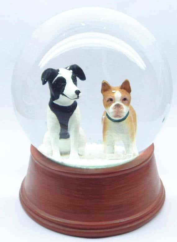 A snowglobe with two dog figurines inside.