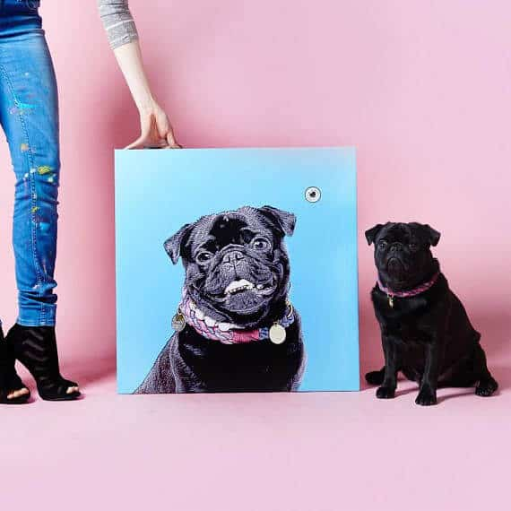 A black pug sits next to a custom portrait of themselves.