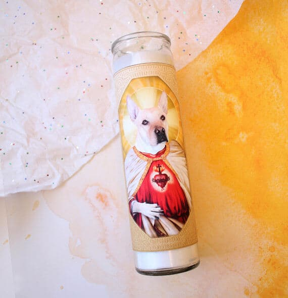 A religious candle with a dog saint on it.