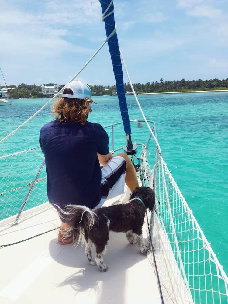 A man and his dog sit at the helm of a sailboat.