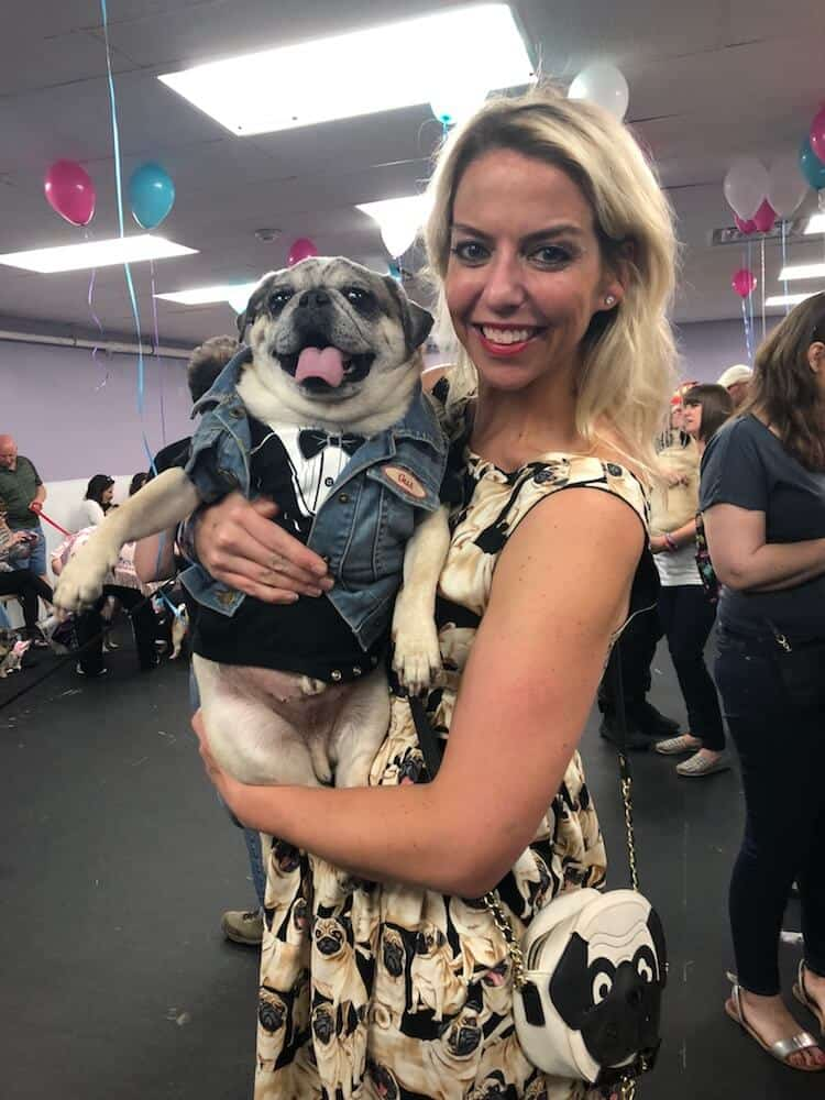 A woman in a pug dress holds her pet pug at a pug prom.