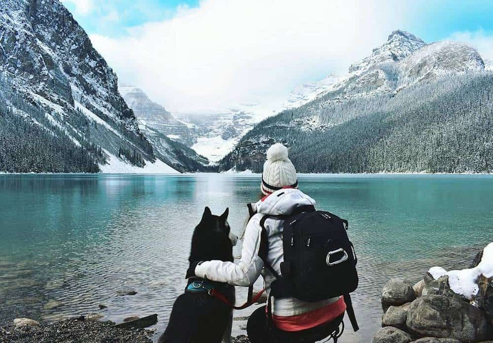 A Husky and his owner enjoy the view of a lake.