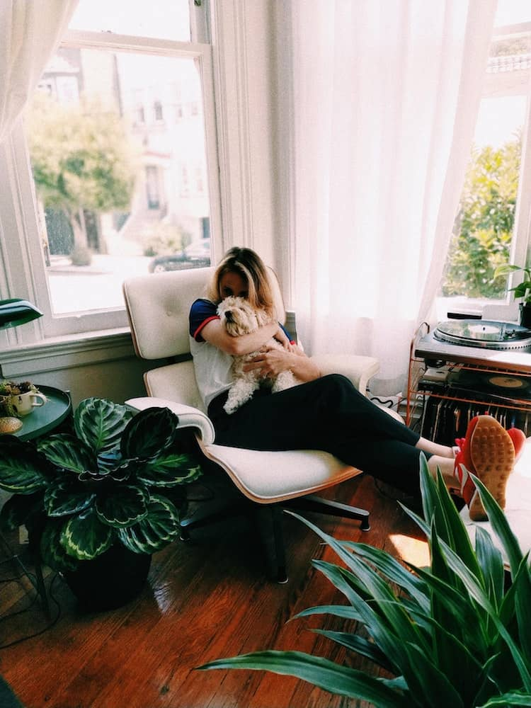 A girl cuddles her dog by a window.