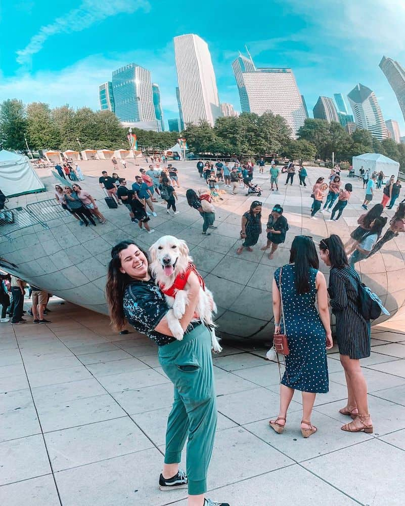 A girl and dog in front of the Bean in Chicago.
