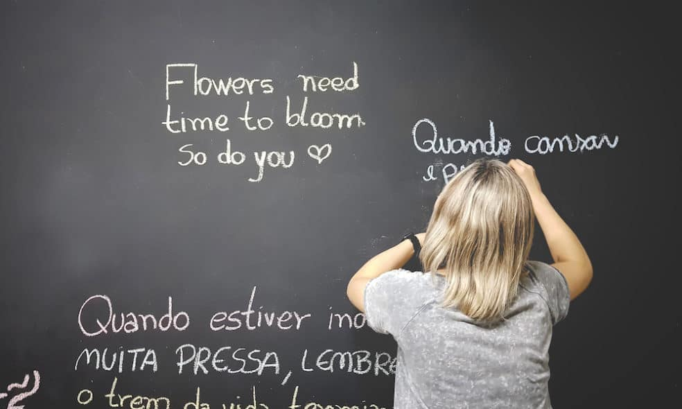 A woman writes in Portuguese on a blackboard.