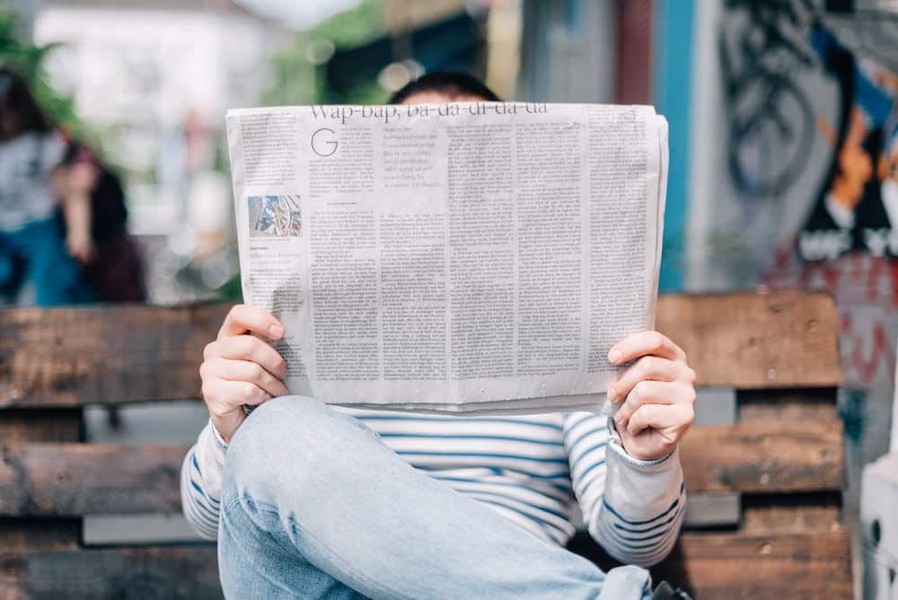A man holds and reads a newspaper.