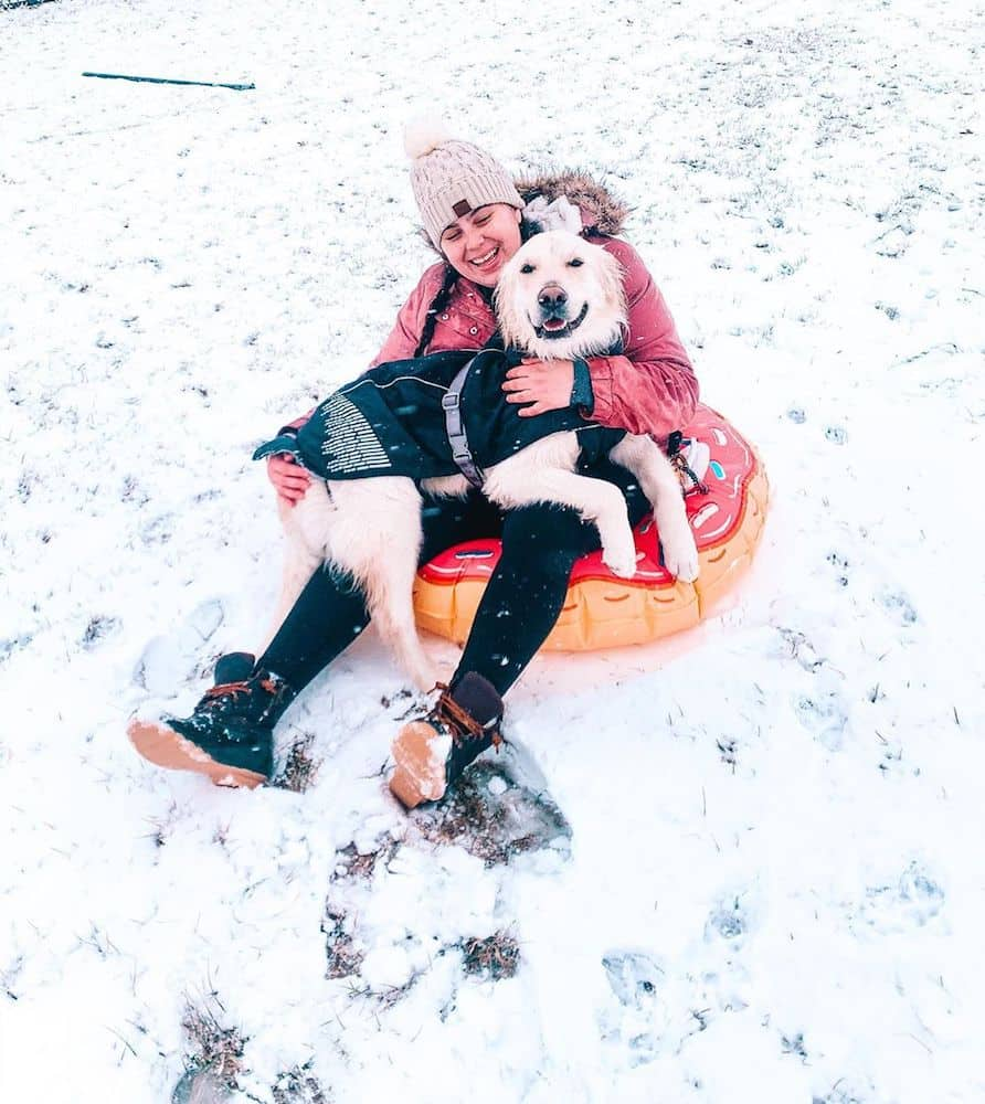 A girl and a dog in a snow tube.