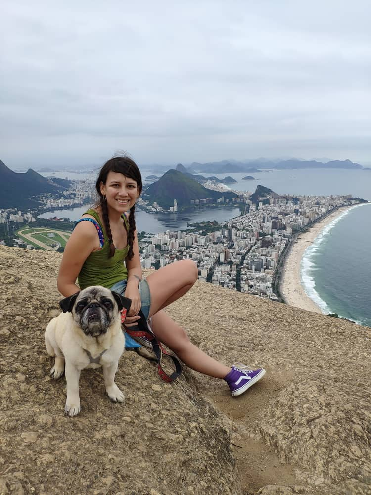 A girl and dog pose at the top of Dois Irmãos.