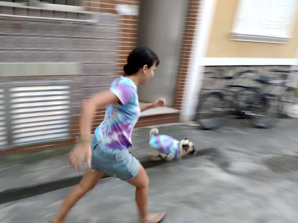A girl and dog run in matching tie dye